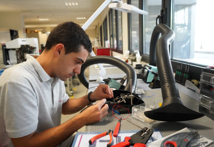 technician welding cables in the manufacturing department