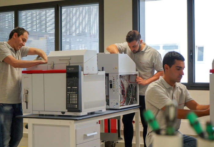 analytical instrumentation in manufacturing by three technicians